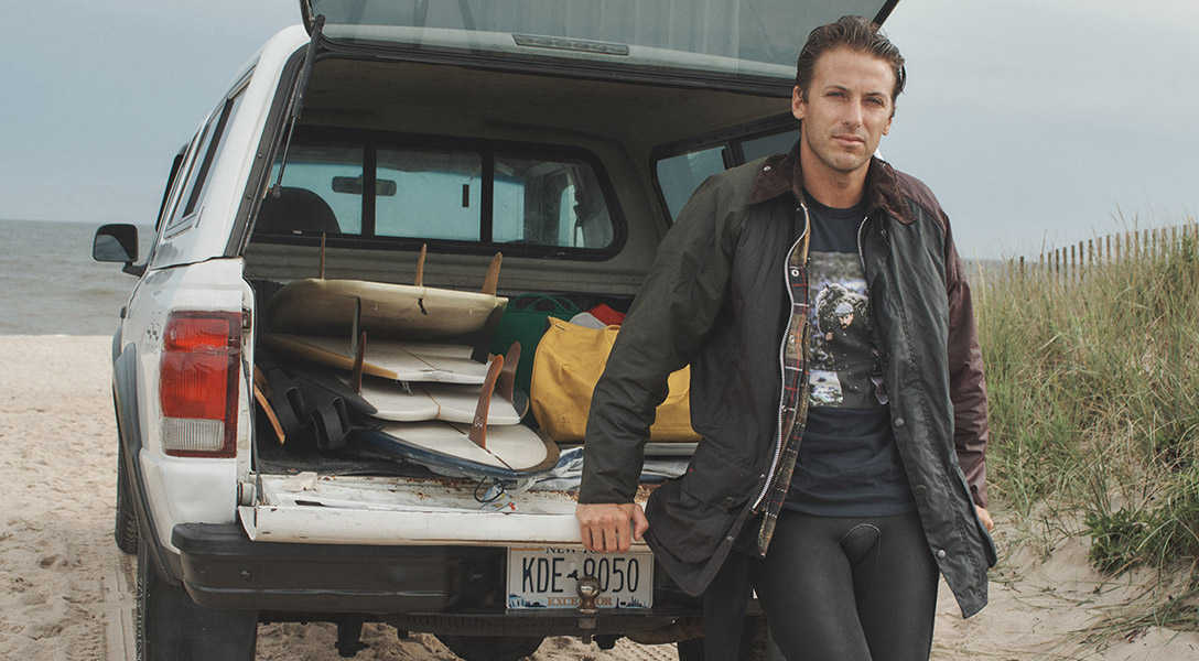 a surfer styles the Barbour X Noah collection at the beach