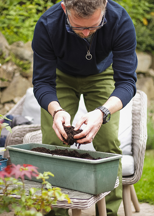 Richard Chivers adding soil to his plant pot