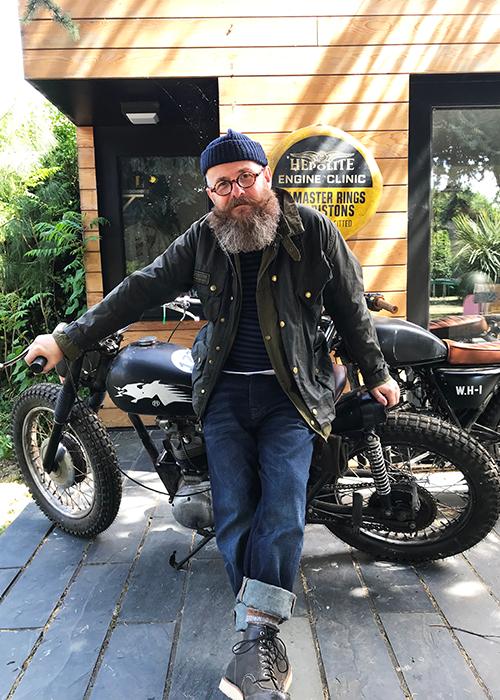 Nige Vallis wearing Barbour International standing by his motorcycle